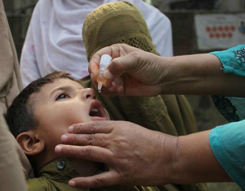 Một em bé Pakistan được cho uống văcxin. Ảnh: TIME.